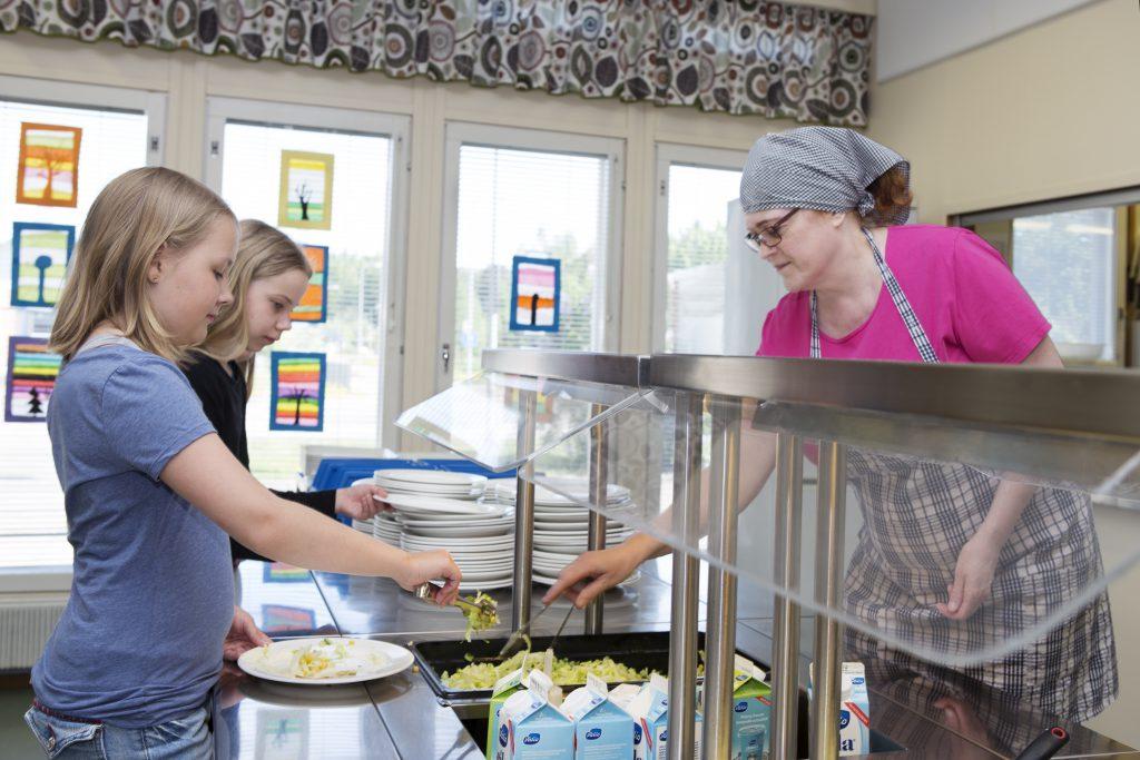 Oppilaat ja ruokalan keittäjä ruokasalin linjastolla.