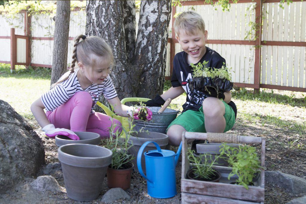Oppilaat puutarhatöissä.